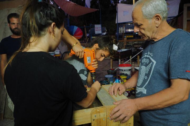הכנת אדניות ממשטחים עם יוסי מזרחי בימי הפסטיבל, בחצר ביתם של דוד וסיגל. צילום- טל גליק