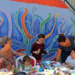 פעילות יצירה לילדים בימי הפסטיבל על רקע ציור קיר של לורה אקרמן, שצויר בעזרת מתנדבות ותלמידי התיכונים. צילום- טל גליק