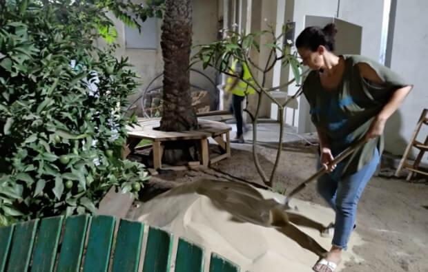 אמא מתנדבת מפזרת חול בחצר הגן באישון לילהאמא מתנדבת מפזרת חול בחצר הגן באישון לילה