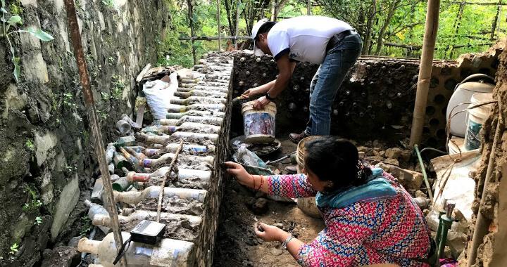 בניה אקולוגית מבקבוקים שהפכה לסימן ההיכר של הארגון. מצולמים: קרישנה ולילה גורונג, מובילי הארגון
